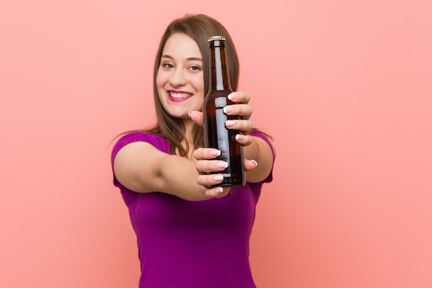 ビール瓶を保持している若い白人女性 Premium写真