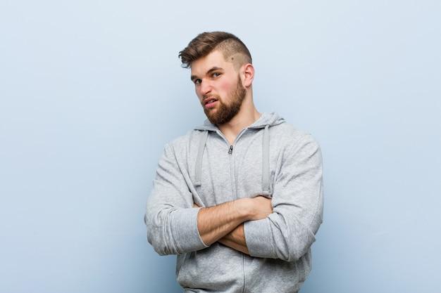 若いハンサムなフィットネス男の頭の後ろに触れる、考えて、選択をします。 Premium写真