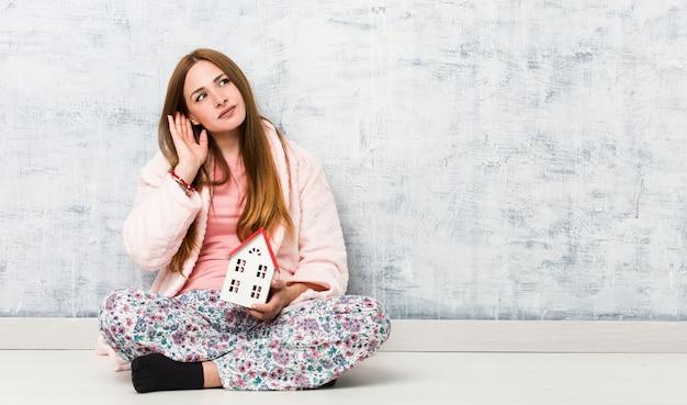 Молодая кавказская женщина держа значок дома пробуя слушать сплетню. Premium Фотографии