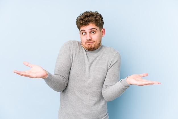 Человек молодого белокурого вьющиеся волосы кавказский изолировал сомневаться и пожимающ плечами в спрашивая жесте. Premium Фотографии