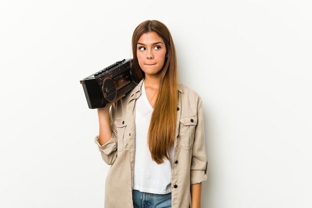 ゲットーブラスターを保持している若い白人女性は混乱し、疑念と不安を感じています。 Premium写真