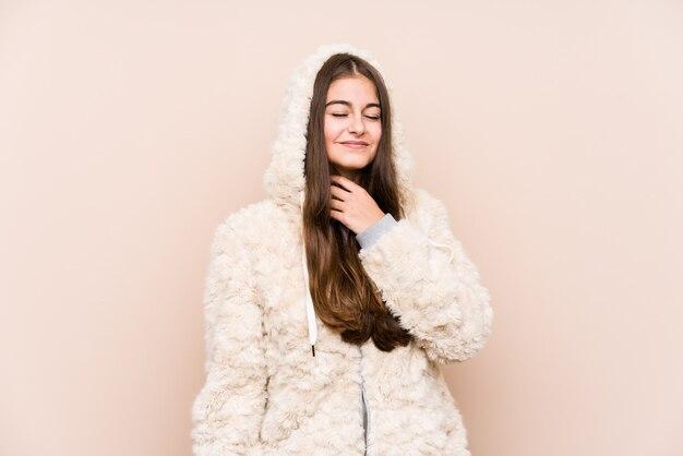孤立したポーズの若い白人女性は、ウイルスや感染症のため喉の痛みに苦しんでいます。 Premium写真