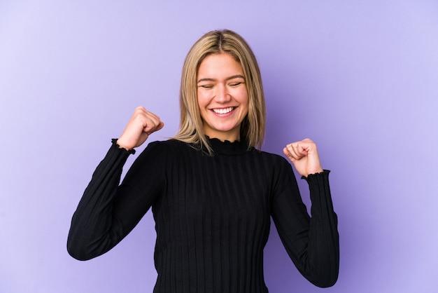 Молодая белокурая кавказская женщина изолировала праздновать победу, страсть и энтузиазм, счастливое выражение. Premium Фотографии