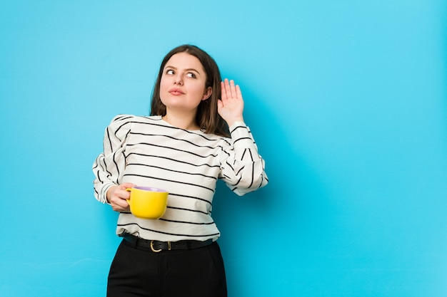 Молодые плюс размер женщина держит кружку чая, пытаясь слушать сплетни. Premium Фотографии