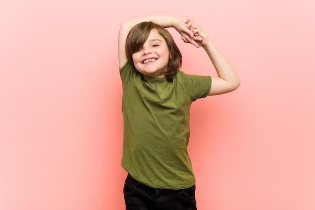 小さな男の子が腕を伸ばして、リラックスした位置。 Premium写真