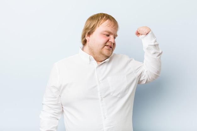 勝利、勝者の概念の後拳を上げる若い本物の赤毛デブ男。 Premium写真