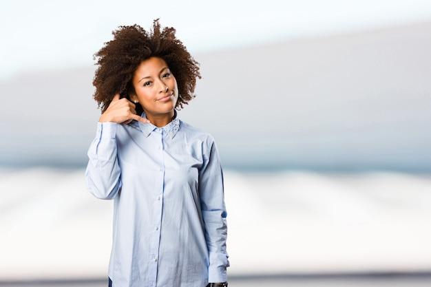 Молодая черная женщина, делая телефонный жест Premium Фотографии