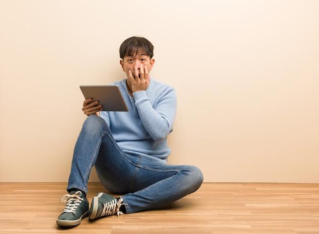 彼のタブレットを使用して座っている若い中国人男性 Premium写真