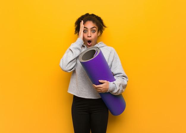 Молодой фитнес черная женщина удивлена и шокирована. держа коврик. Premium Фотографии