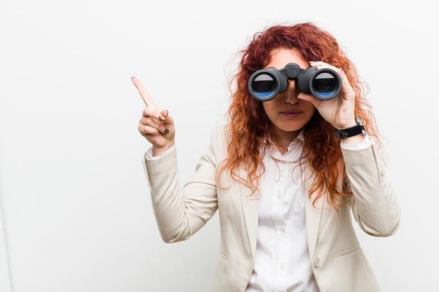 人差し指で元気に指している笑顔双眼鏡を保持している若い白人ビジネス赤毛の女性。 Premium写真