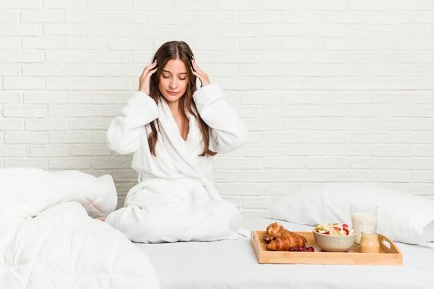 寺院に触れると頭痛を持つベッドの上の若い女性 Premium写真