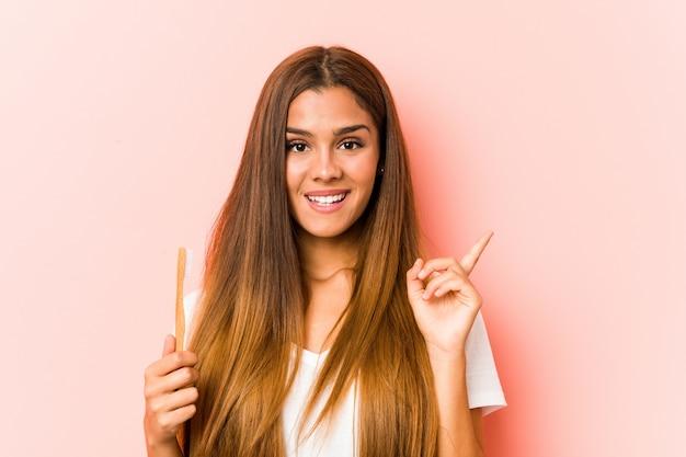 人差し指で元気に指している笑顔の歯ブラシを保持している若い女性 Premium写真