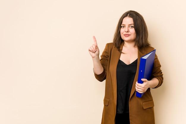 Молодой бизнес женщина, держащая файлы, показывая номер один с пальцем Premium Фотографии