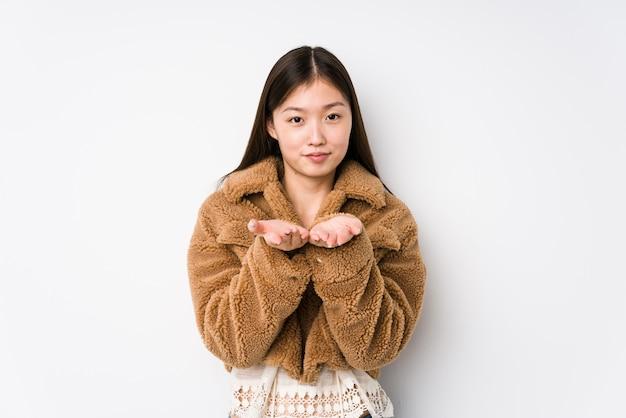 若い女性が手のひらで何かを保持してポーズ Premium写真