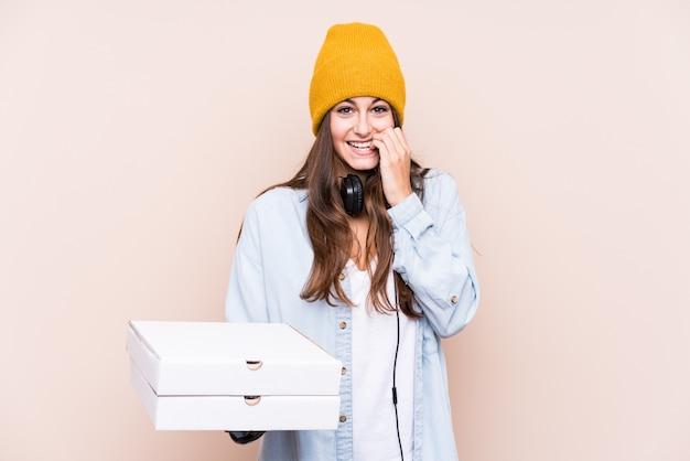 爪を噛むピザを保持している若い白人女性、神経質で非常に心配しています。 Premium写真