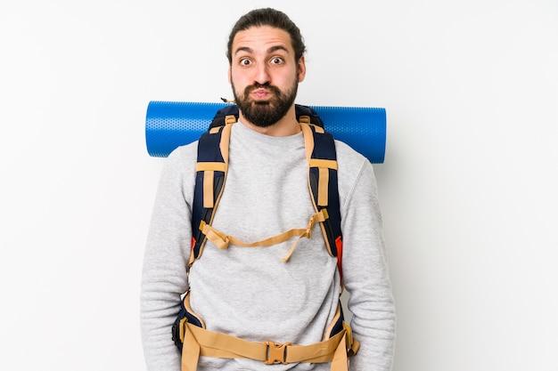 白い壁の若いバックパッカーの男は頬を吹く、疲れた表情をしています。 Premium写真