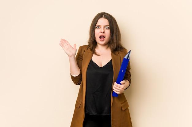 Молодой бизнес женщина, держащая файлы удивлен и шокирован. Premium Фотографии