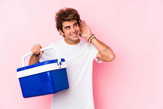 Молодой человек держит портативный холодильник, пытаясь слушать сплетни Premium Фотографии