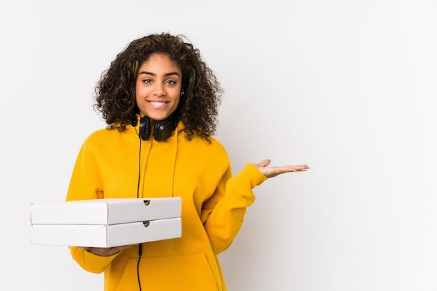 手のひらにコピースペースを表示し、腰に別の手を保持しているピザを保持している若い学生女性 Premium写真