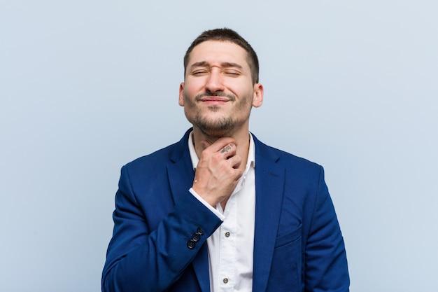 若いビジネス白人男性がウイルスのため喉の痛みに苦しんでいます。 Premium写真