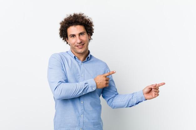 Молодой кудрявый зрелый мужчина в элегантной рубашке возбужденно указывая указательными пальцами Premium Фотографии