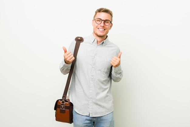 両方の親指を上げる、笑顔と自信を持って若いビジネスマン Premium写真