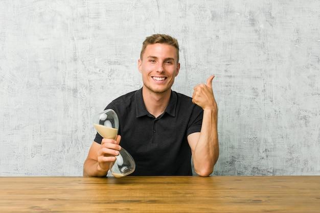 Молодой человек держит песочный таймер на столе, поднимая оба больших пальца вверх, улыбаясь и уверенно Premium Фотографии