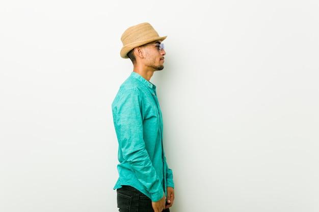 Молодой латиноамериканский человек в летней одежде, глядя влево Premium Фотографии