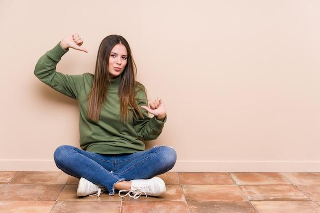 床に座っている若い白人女性は誇りに思って、自信を持って、次の例です。 Premium写真