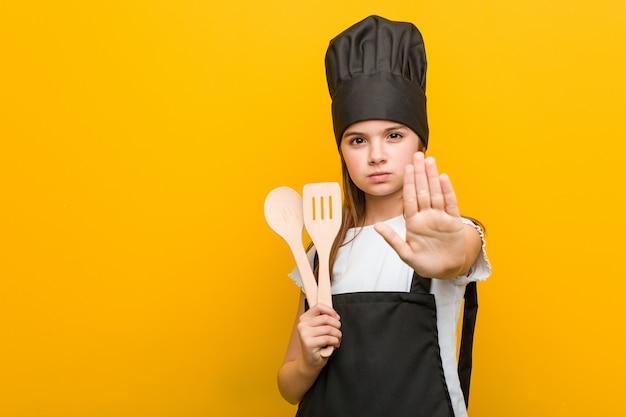 Маленькая кавказская девушка нося костюм шеф-повара стоя при протягиванный знак стопа показа руки, предотвращая вас. Premium Фотографии