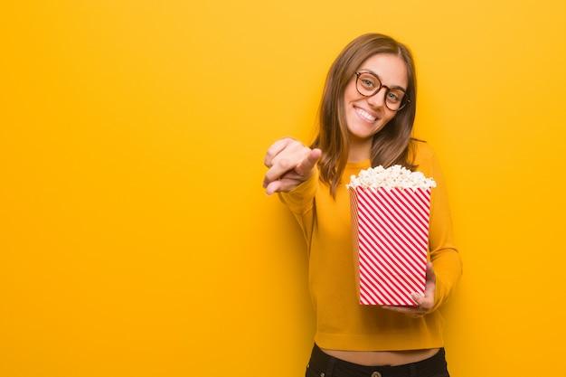 Молодая милая кавказская женщина жизнерадостная и усмехаясь указывать Premium Фотографии