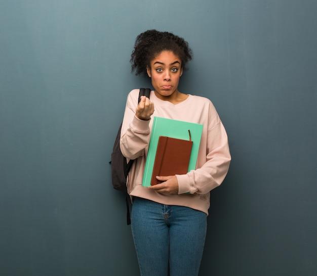 Молодой студент черная женщина делает жест необходимости. Premium Фотографии