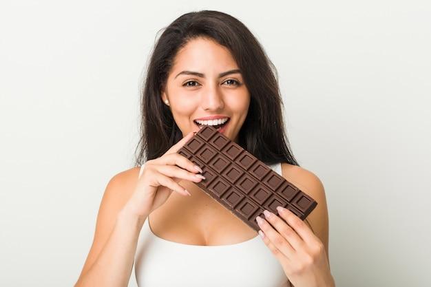 チョコレートタブレットを保持している若いヒスパニック系女性 Premium写真