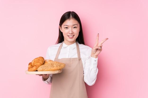 Молодая китайская женщина хлебопека показывая номер два с пальцами. Premium Фотографии