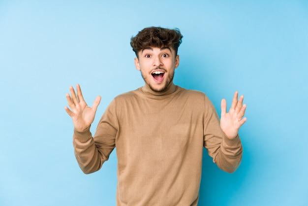 快活な驚きを受けて興奮し、手を上げる分離された若い男 Premium写真