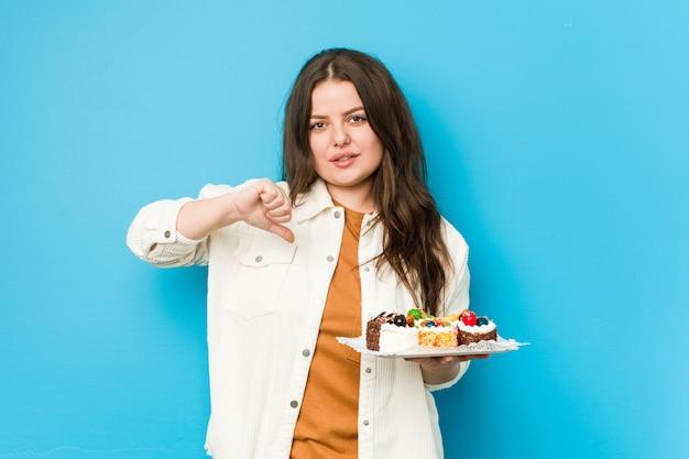 嫌いなジェスチャー、親指ダウンを示す甘いケーキを保持している若い女性 Premium写真
