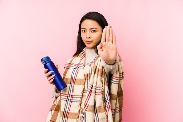 Молодая китайская женщина делая располагаться лагерем изолированный на розовой смущенной стене, чувствует сомнительным и неуверенным. Premium Фотографии