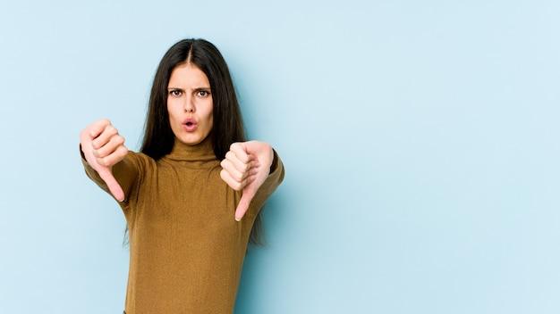 水色の壁に親指を示すと嫌悪感を表現する若い白人女性。 Premium写真