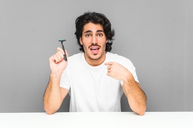 Молодой человек, держащий лезвие бритвы, удивленно указывает на себя, широко улыбаясь. Premium Фотографии