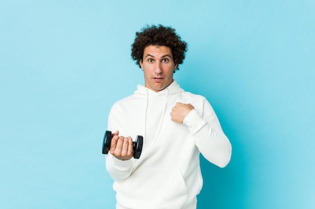 Спортивный мужчина держит гантели удивленно указывая на себя, широко улыбаясь. Premium Фотографии