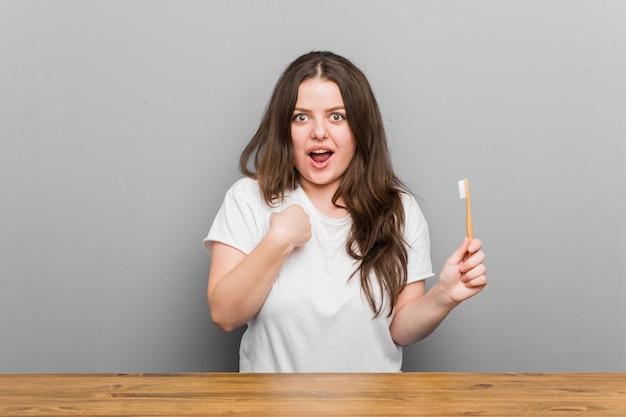 Молодой плюс размер соблазнительной женщины, держащей зубную щетку, удивленно указывает на себя, широко улыбаясь. Premium Фотографии