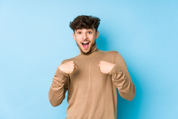 孤立した若いアラビア人は、指で驚いて指を広げて、広く笑っています。 Premium写真