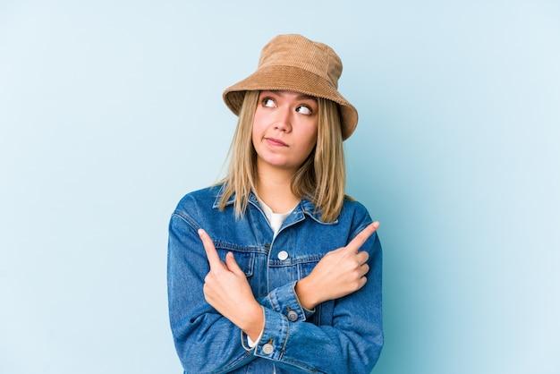 Молодая блондинка кавказская женщина указывает в сторону, пытаясь выбрать один из двух вариантов. Premium Фотографии