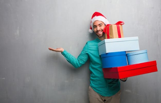 手で何かを持っている贈り物を保持しているサンタの帽子を着て Premium写真