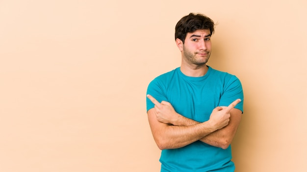 Молодой человек на бежевой стене указывает в сторону Premium Фотографии