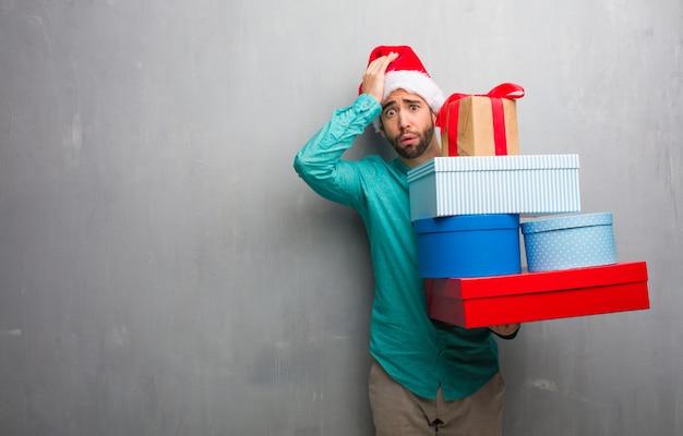 贈り物をしているサンタの帽子を身に着けている若い男は心配し、圧倒した Premium写真