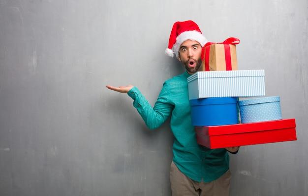 手のひらに何かを持っている贈り物を保持しているサンタの帽子を着て Premium写真