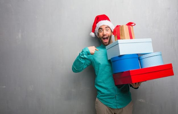 プレゼントを持っているサンタの帽子を身に着けている若い男は、驚いて、成功し、繁栄を感じる Premium写真