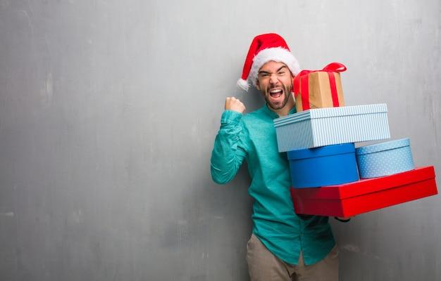 プレゼントを抱いているサンタの帽子を着た若い男は驚いてショックを受けました Premium写真