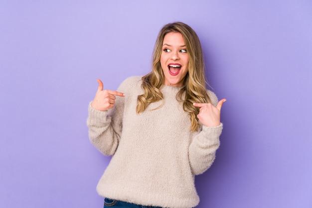 Молодая кавказская женщина изолированная на пурпуре удивила указывать с пальцем, широко улыбаясь. Premium Фотографии